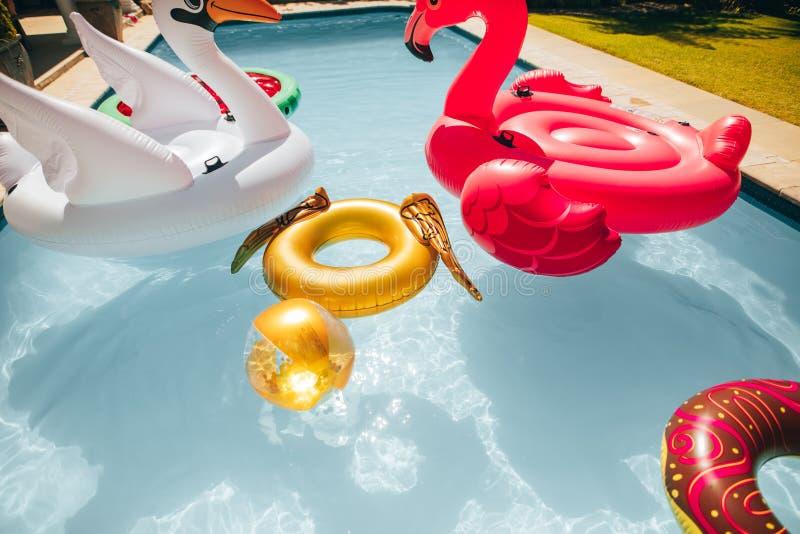Kleurrijk opblaasbaar speelgoed die in een pool drijven stock foto's