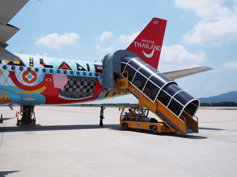 Kleurrijk passagiersvliegtuig met het inschepen van helling bij de schort stock foto