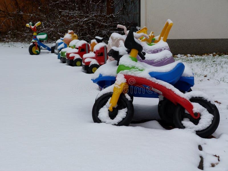Kleurrijk plastic jonge geitjesspeelgoed in speelplaats met sneeuwdekking stock afbeelding
