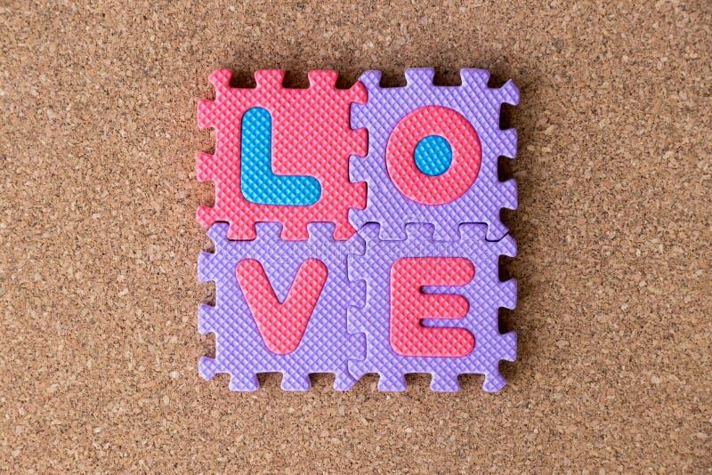 Kleurrijk stuk speelgoed schuimalfabet in woordliefde op cork raadsachtergrond royalty-vrije stock fotografie