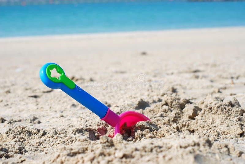Kleurrijk stuk speelgoed in zand op een strand royalty-vrije stock afbeeldingen