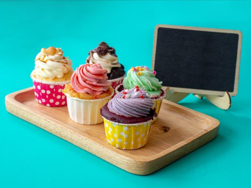 Kleurrijk van eigengemaakte cupcake met lege bord en exemplaarruimte voor uw tekst Cupcake op houten Dienblad op groene achtergro royalty-vrije stock afbeelding