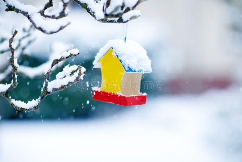 Kleurrijk vogelhuis in de winter in openlucht sneeuwval Vogel het voeden concept stock foto's