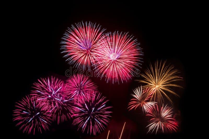 Kleurrijk vuurwerk over nachthemel, rode vuurwerklijnen stock afbeelding