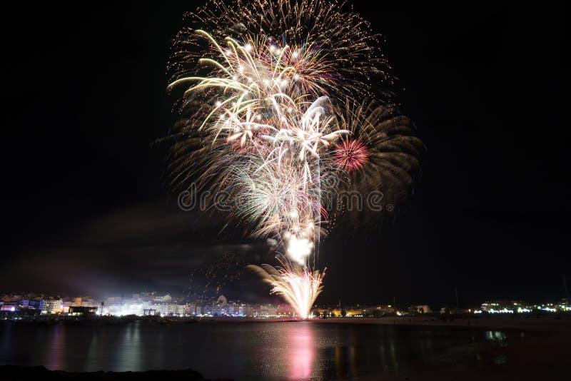 Kleurrijk vuurwerk over overzees stock afbeelding