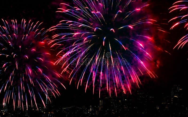 Kleurrijk Vuurwerk over Stadshorizon en Rivier met Zwarte Hemelachtergrond stock afbeeldingen