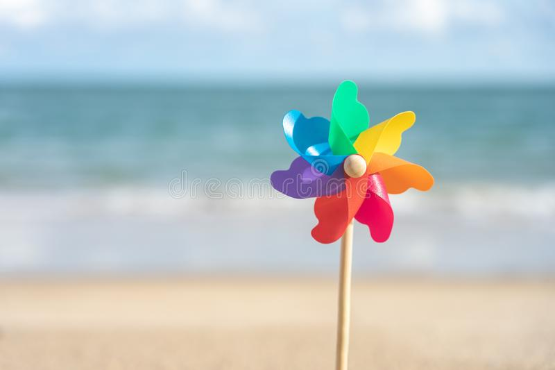 Kleurrijk windmolendocument dat op de strand Overzeese mening in de dag met een blauwe achtergrond wordt geborduurd Het concept v stock fotografie