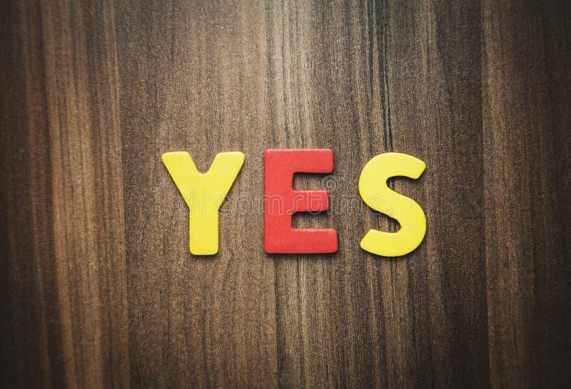 Kleurrijk woord ja op de houten achtergrond stock foto's