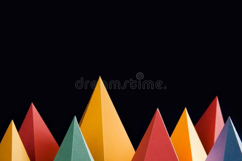 Kleurrijke abstracte geometrische vormen op zwarte achtergrond Driedimensionele driehoekige piramide Geel blauw roze malachiet stock foto