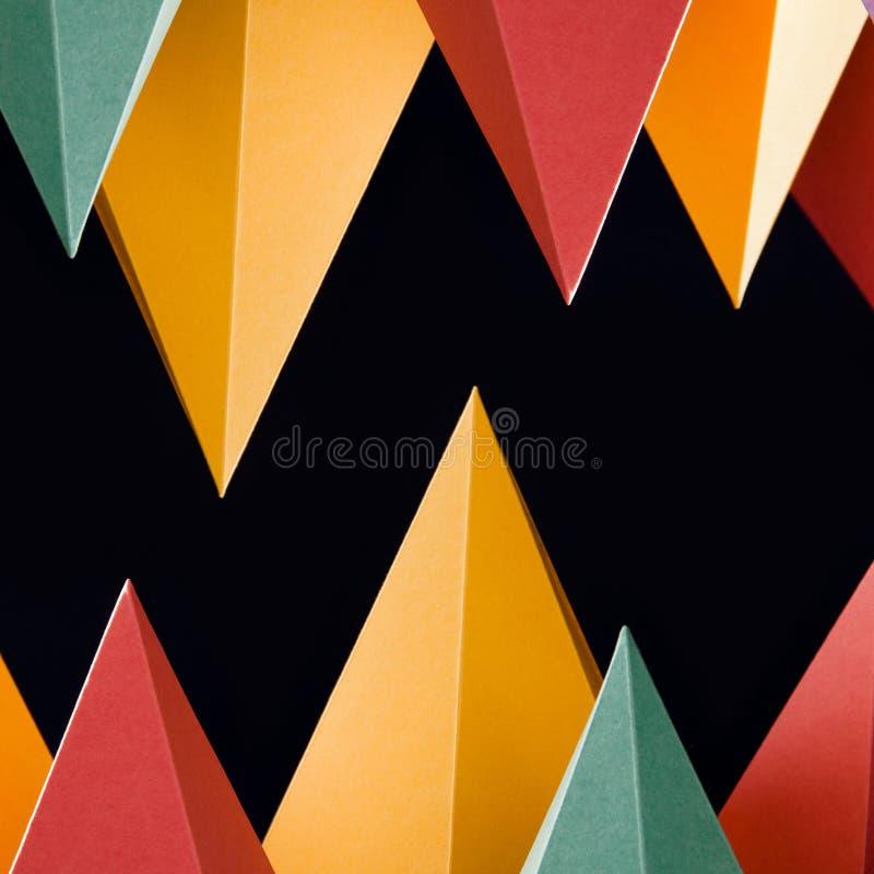 Kleurrijke abstracte geometrische vormen op zwarte achtergrond Driedimensionele driehoekige piramide Geel blauw roze malachiet royalty-vrije stock foto