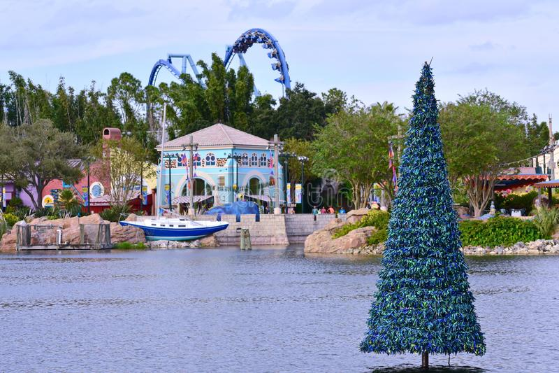 Kleurrijke Afrikaanse stijlarchitectuur, varende boot en Kerstboom op lichtblauwe bewolkte bac stock afbeelding