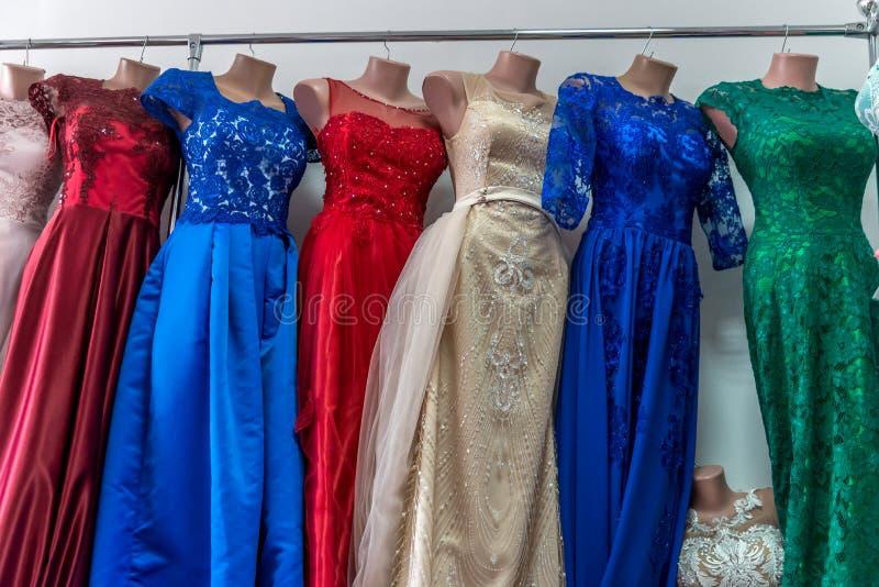 Kleurrijke avonduitrustingen op ledenpoppen in salon stock foto