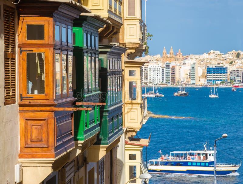 Kleurrijke balkons van Valletta met toeristenboot - Malta stock foto's