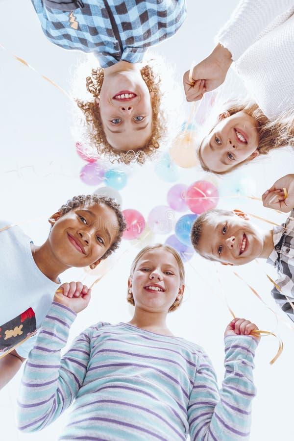 Kleurrijke ballons die boven jonge geitjes hangen stock foto