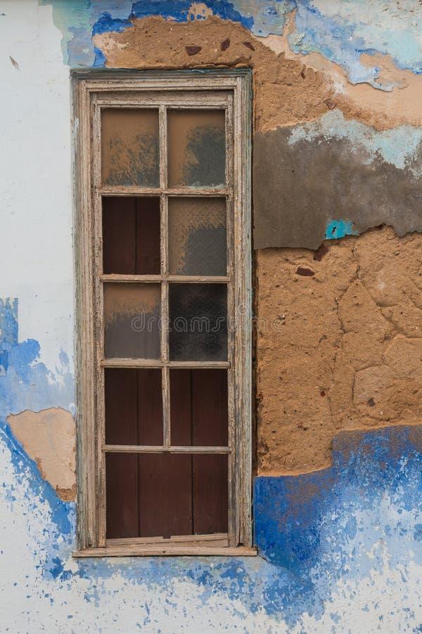 Kleurrijke beschadigde muur met een gebroken venster stock afbeeldingen