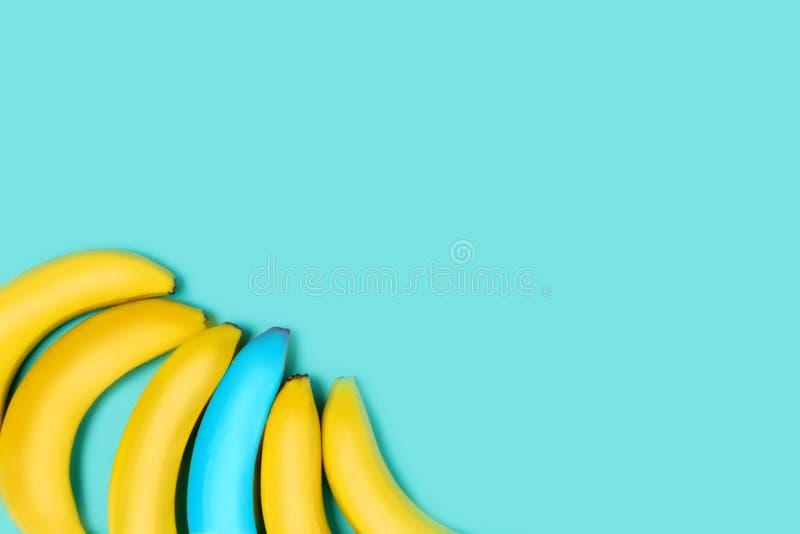 Kleurrijke blauwe achtergrond voor tekst en reclame Gele en één blauwe banaan in de hoek van het beeld stock foto