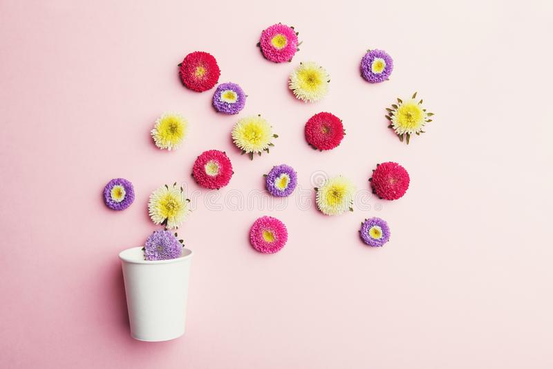Kleurrijke bloemen en document koffiekop op roze achtergrond stock foto
