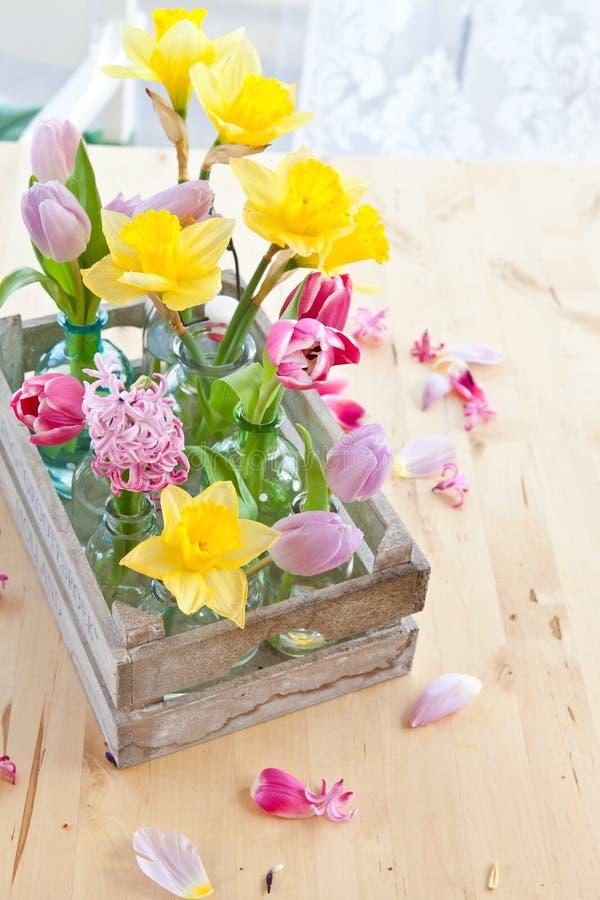 Kleurrijke bloemen in kleine flessen stock foto's