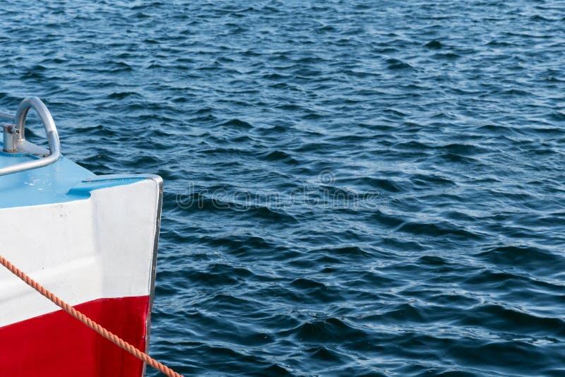 Kleurrijke boog van een boot in gegolft water stock afbeelding