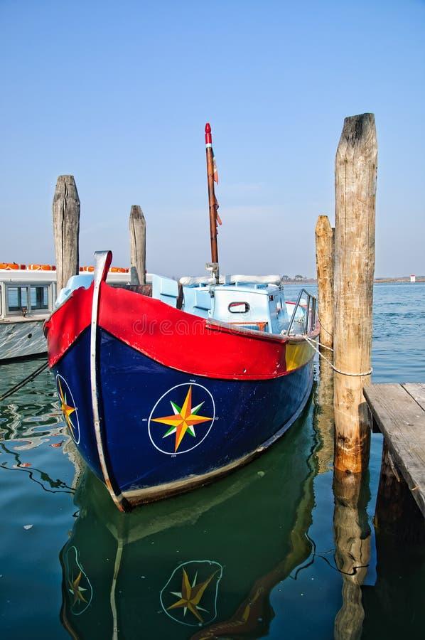 Kleurrijke boot die dichtbij de pijler wordt vastgelegd stock foto's