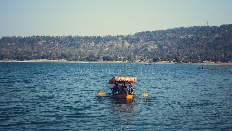 Kleurrijke boot in landschap van meer stock fotografie
