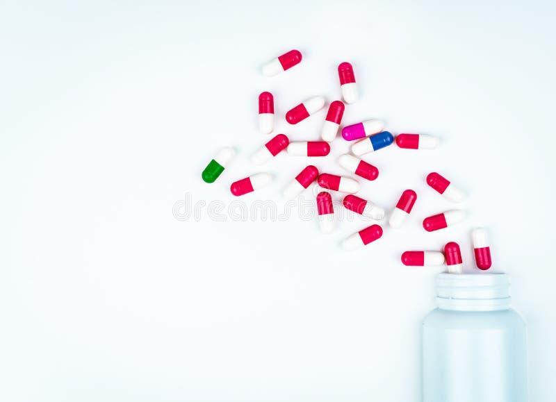 Kleurrijke capsulepillen die uit plastic drugfles worden uitgespreid De achtergrond van de apotheek Farmaceutische Industrie Drug stock afbeelding