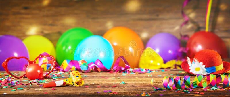 Kleurrijke carnaval of verjaardagsachtergrond met partijhoed en ballonnen stock afbeelding