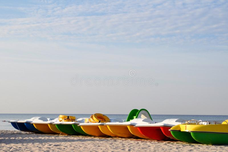 Kleurrijke catamarans dichtbij de overzeese kust op een verlaten strand bij dageraad horizontaal Conceptentoerisme, vakantie door royalty-vrije stock afbeelding