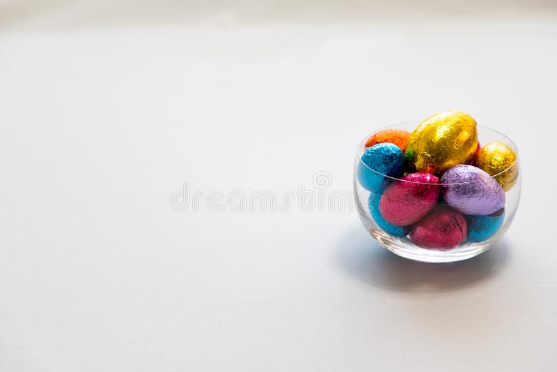 Kleurrijke chocoladepaaseieren in een transparante kom die met whit achtergrond wordt ge?soleerd stock afbeeldingen