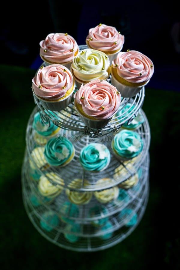 Kleurrijke Cupcakes op cakestand tegen donkere achtergrond royalty-vrije stock afbeeldingen
