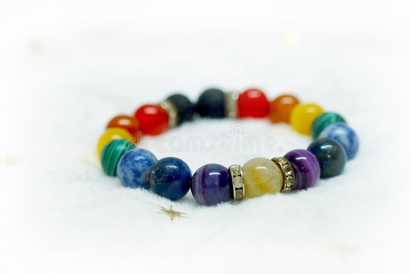 Kleurrijke de armbandparel van de spectrum gelukkige steen op witte handdoekachtergrond de manier met gelooft in Add charme, gezo stock foto