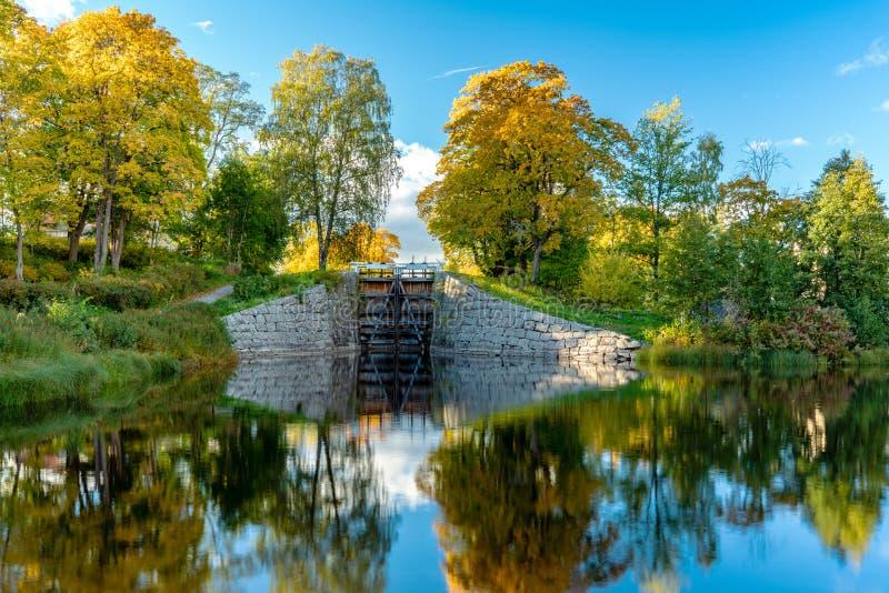 Kleurrijke de herfstmening van een kanaalslot met vlotte spiegel zoals water stock foto