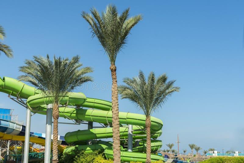 Kleurrijke dia's en pool in aquapark Plaats om een rust en een familiepret te hebben Lange, groene waterslide in aquapark zonnig royalty-vrije stock foto