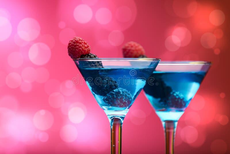 Kleurrijke die cocktails met bessen, achtergrond met lichteffecten worden versierd stock foto