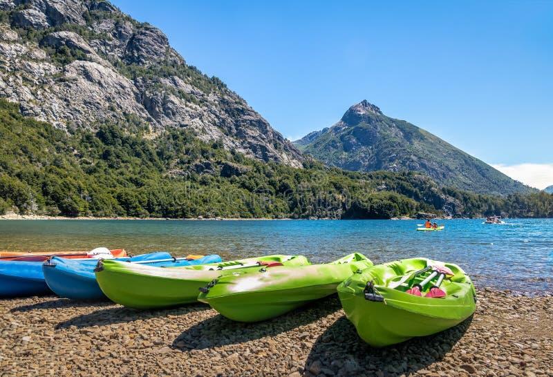 Kleurrijke die Kajaks in een meer door bergen in Bahia Lopez in Circuito Chico - Bariloche, Patagonië, Argentinië wordt omringd royalty-vrije stock afbeeldingen