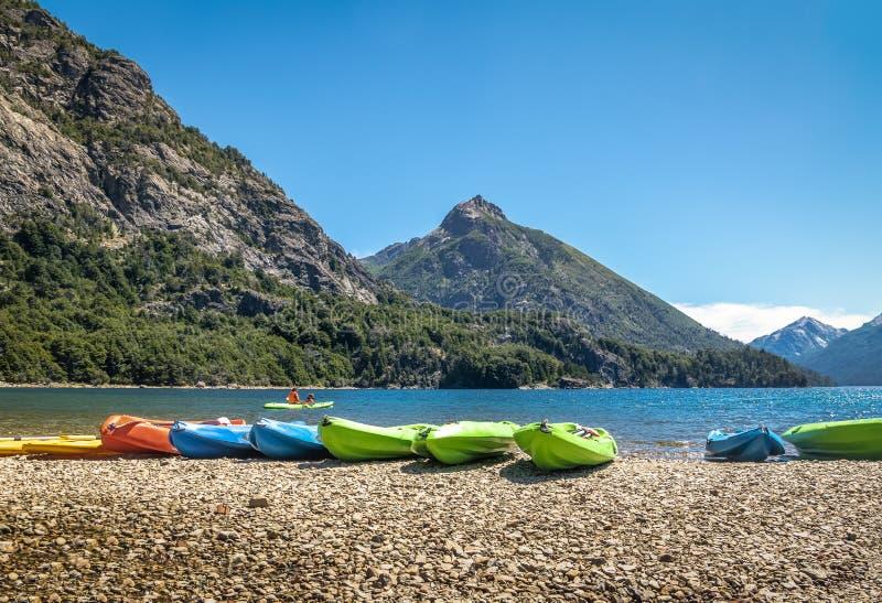 Kleurrijke die Kajaks in een meer door bergen in Bahia Lopez in Circuito Chico - Bariloche, Patagonië, Argentinië wordt omringd royalty-vrije stock afbeelding