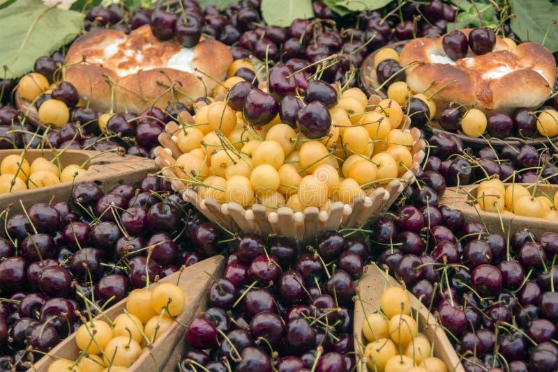 Kleurrijke die kersen met Bulgaarse volks houten kommen en eigengemaakt brood met kaas worden verfraaid royalty-vrije stock afbeelding