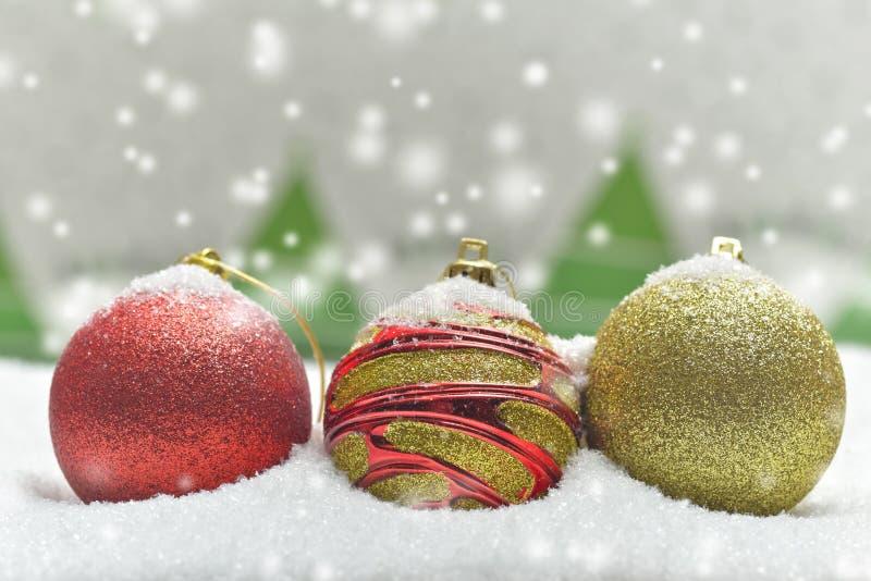 Kleurrijke die Kerstmisbollen door sneeuw met bomen worden omringd royalty-vrije stock afbeeldingen