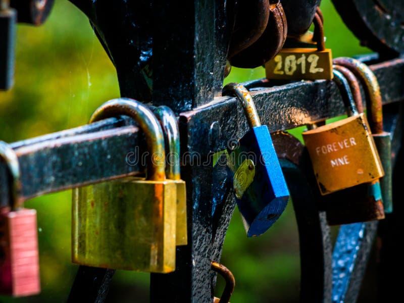 Kleurrijke die liefdesloten op brug worden gehangen stock afbeeldingen
