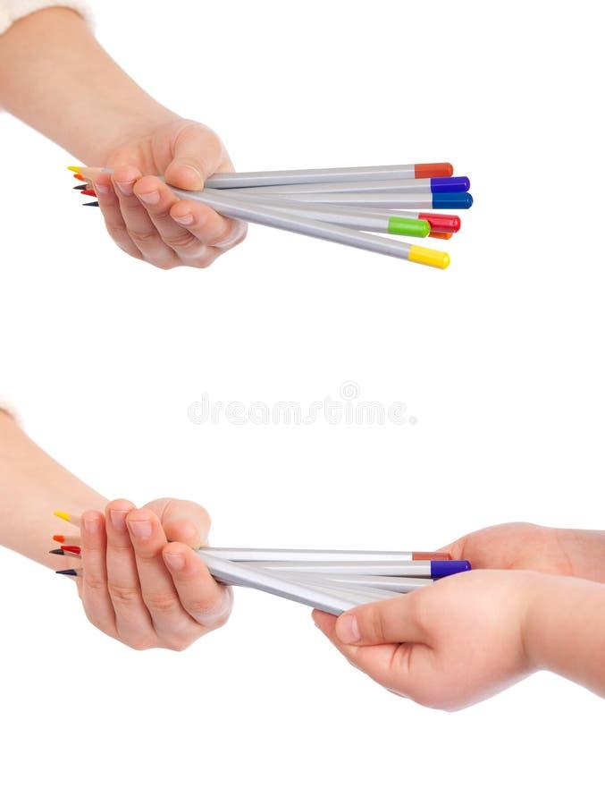 Kleurrijke die potloden in kindhanden op wit worden geïsoleerd royalty-vrije stock afbeelding