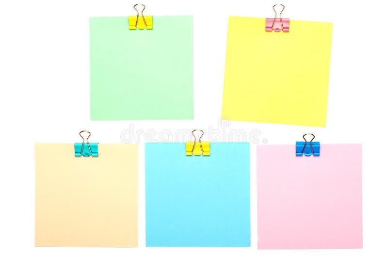 Kleurrijke die Stoknota's met papercliphouders op witte achtergrond worden geïsoleerd Spot omhoog stock afbeeldingen