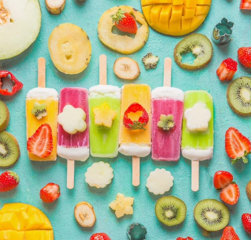 Kleurrijke diverse Roomijsijslollys met verse gesneden vruchten en besseningrediënten op lichtblauwe achtergrond, hoogste mening, royalty-vrije stock foto