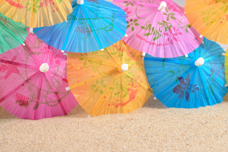 Kleurrijke document cocktailparaplu's in zand stock afbeeldingen