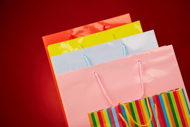 Kleurrijke document het winkelen zakken op rood stock fotografie