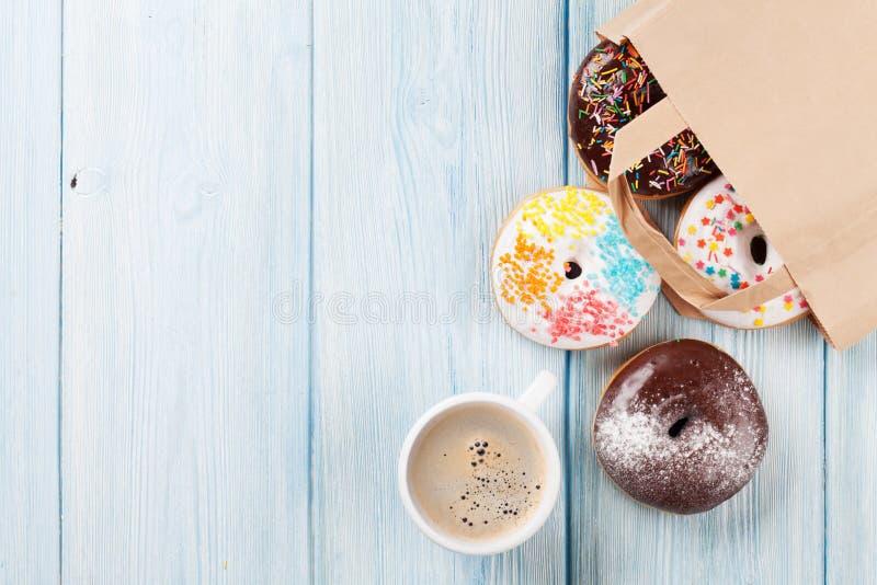 Kleurrijke donuts in document zak en koffiekop royalty-vrije stock afbeelding