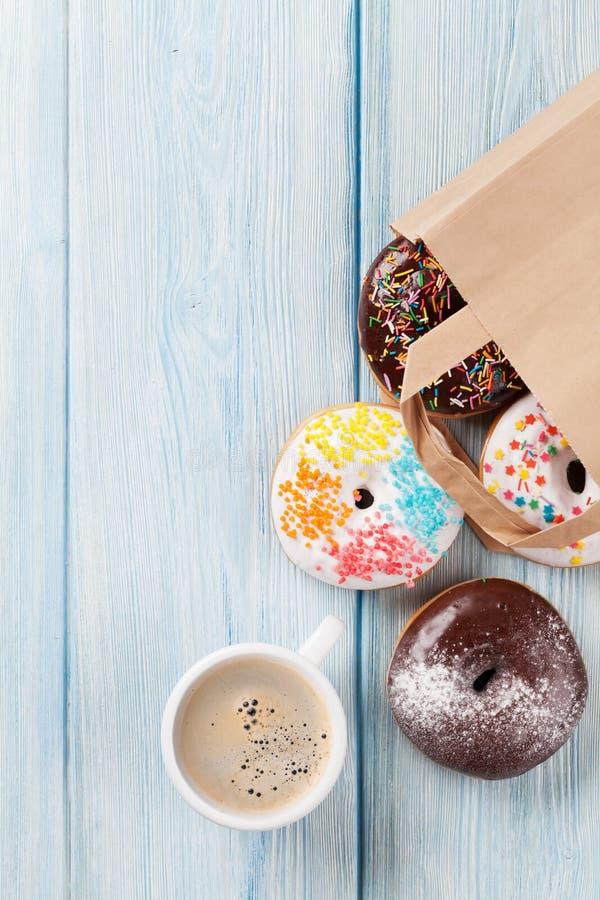 Kleurrijke donuts in document zak en koffiekop royalty-vrije stock foto