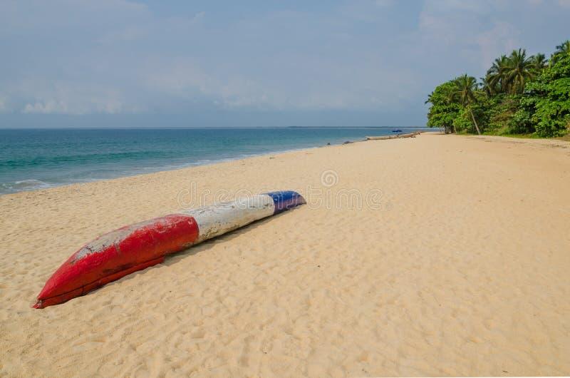Kleurrijke dugout vissersboot die op verlaten tropisch strand in Robertsport, Liberia, West-Afrika leggen royalty-vrije stock afbeelding