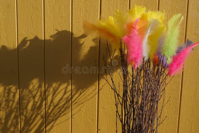 Kleurrijke Easterfeathers tegen gele voorgevel stock foto's