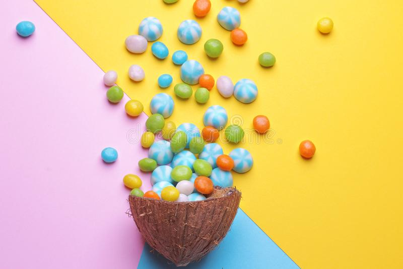 Kleurrijke explosie van snoepjes in een kokosnoot op heldere multi-colored achtergronden, creatief stilleven stock fotografie
