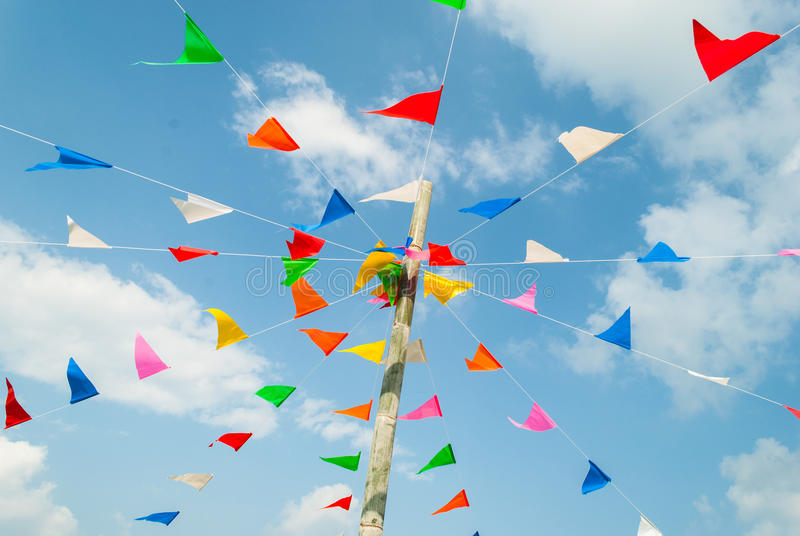Kleurrijke feestelijke bunting vlaggen tegen, op blauw en wolkenhemel royalty-vrije stock fotografie